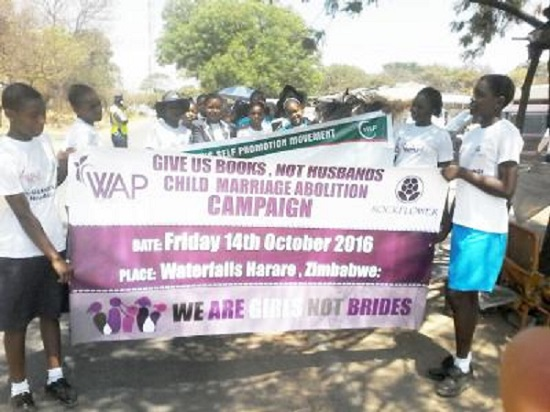 Family law reform advocates hold campaign signs on International Day of the Girl Child